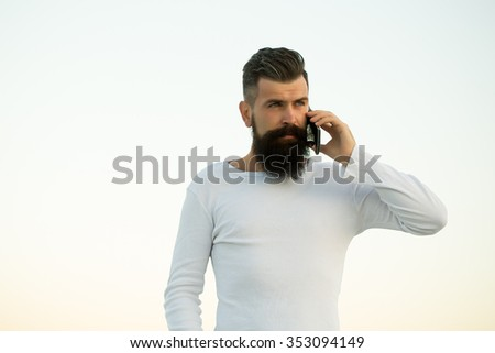 One handsome young bearded serious business man in white sweater holding and speaking on cell phone outdoor on light sky natural background, horizontal picture - stock photo