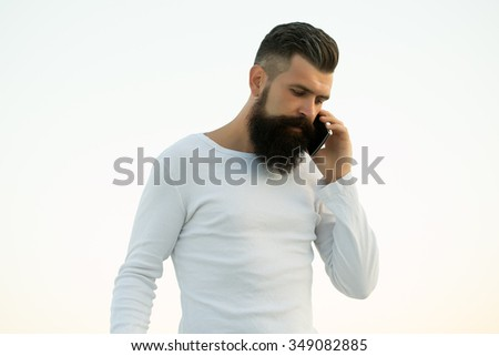 One handsome young bearded thoughtful business man in white sweater holding and speaking on cell phone outdoor on light sky natural background, horizontal picture - stock photo