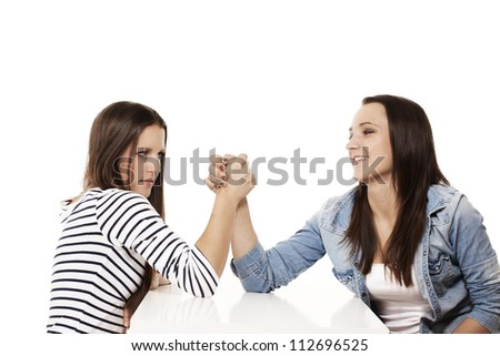 one happy and one strained teenager arm wrestling on white background - stock photo