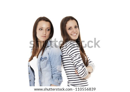 one happy and one upset teenager standing back to back on white background - stock photo