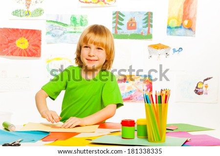 One happy boy on creative craft preschool class with pencils, images and cardboard in the room - stock photo