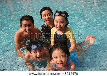 One happy family playing in the pool - stock photo