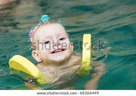 One happy smiling little girl swimming with safety discs at water pool - stock photo