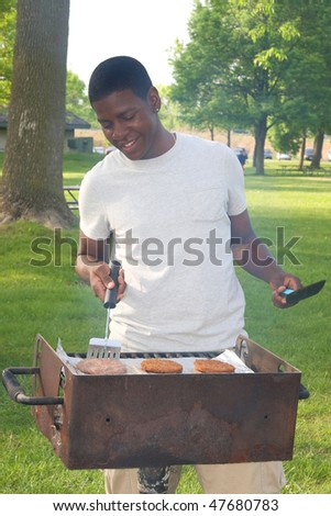one happy twenties African American male cooking on a bbq grill outdoors in a park - stock photo