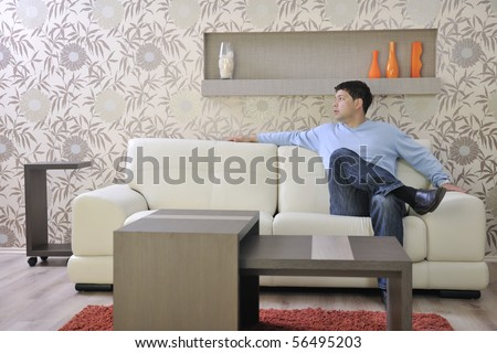 one happy young man relax at home in livingroom with modern style furniture indoor