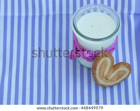 one heart cookies on the purple napkin with glass of milk - stock photo