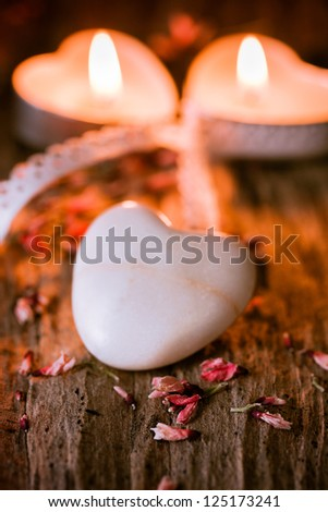 one heart of stone for valentine and 2 candles in the background - stock photo