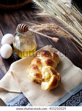 One home baked braided challah loaf for shabbat. Challah bread with sesame seeds. One loaf served with honey, decorated with wheat. - stock photo