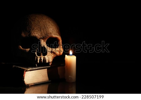 One human skull on old book near lighting candle on dark background - stock photo
