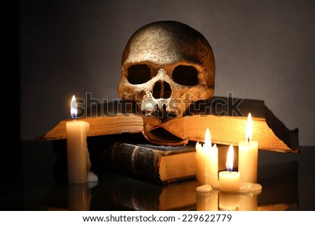 One human skull on old books near lighting candles on dark background - stock photo