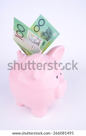 One hundred Australian dollar note inserted into a pink piggy bank - stock photo