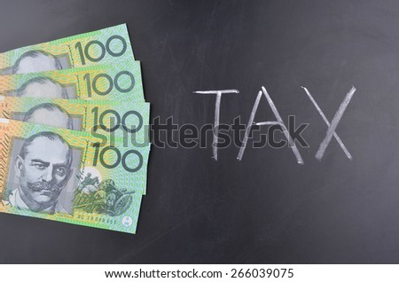 One hundred Australian dollar notes stuck on a blackboard where tax is handwritten in white chalk - stock photo