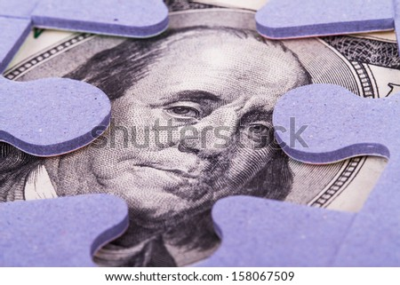 One  hundred dollar banknote between puzzle pieces. - stock photo
