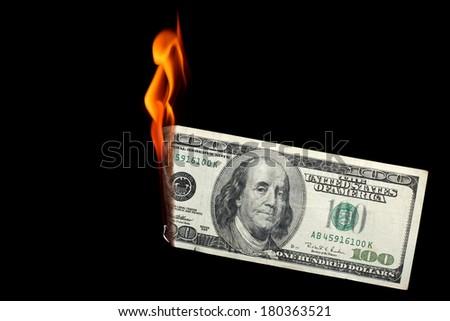 One hundred dollar bill burning on black background - stock photo