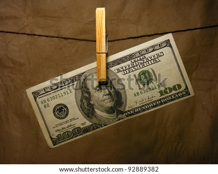 One hundred dollar bill hanging on a clothes pin - stock photo