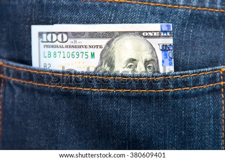 One hundred dollar bill in the pocket of jeans. A portrat of Franklin looks out of a pocket of blue jeans close up