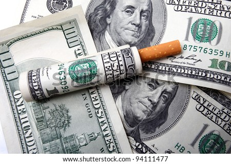 One hundred dollar bill rolled around the cigarette and placed on a few hundred dollar bills - stock photo