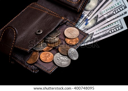 One hundred dollar bills in  dark leather purse isolated on black background - stock photo