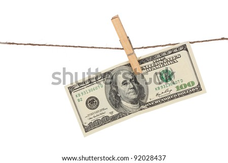 One hundred dollar bills is hanging on a rope with wooden clothespin isolated on white - stock photo