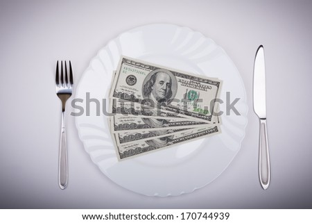 One hundred dollar bills lie on white plate with knife and fork on opposite sides
