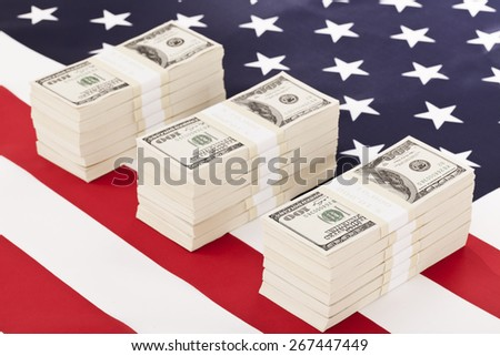 One hundred dollar bills on american flag - stock photo