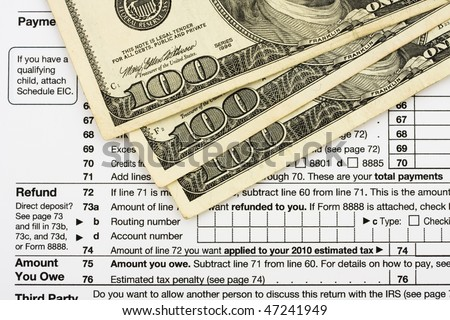 One hundred dollar bills sitting on tax papers, Calculating your tax refund - stock photo