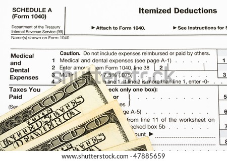 One hundred dollar bills sitting on tax papers, Federal Tax Forms for Items Deductions - stock photo