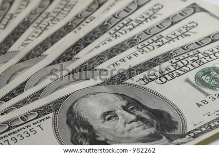 One hundred Dollar Bills with focus First Bill and Medium Depth of Field on Rest - stock photo