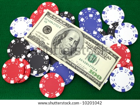 one hundred dollars and several gambling chips over a green table