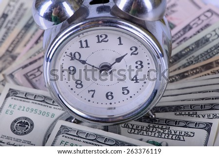 One hundred dollars banknotes and clock alarm