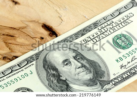 One hundred dollars banknotes on wooden background - stock photo
