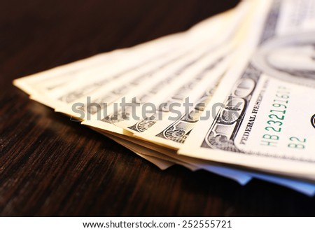 One hundred dollars banknotes on wooden table background - stock photo