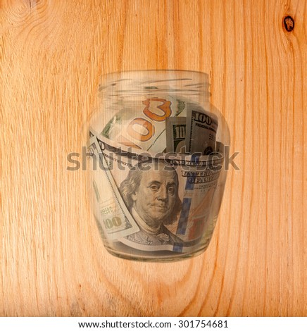 One hundred dollars  bills in a glass jar isolated over wooden background - stock photo