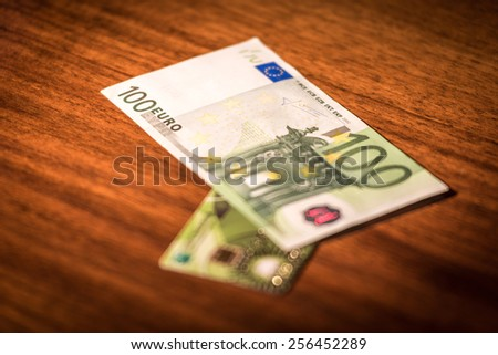 One hundred euros and a credit card lying on a brown glossy table - stock photo