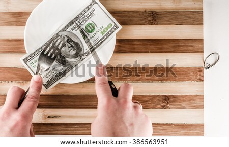 one hundred, fifty dollars a plate with knife and fork - stock photo