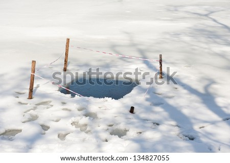 One ice hole and melting snow at the lake winter season. Snow on frozen water surface and four sticks in ice to stop danger. Small lake or pond in Warsaw park in Poland, horizontal orientation, nobody - stock photo