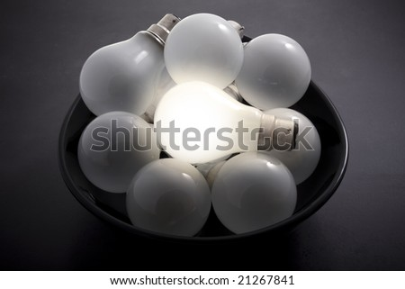 One illuminated light bulb in a pile of dim ones