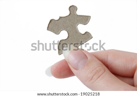 One jigsaw piece held in a hand, ready to solve a puzzle