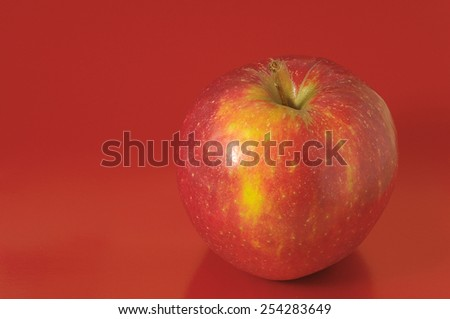 One Juicy Hot Red Apple over a Colored Background - stock photo