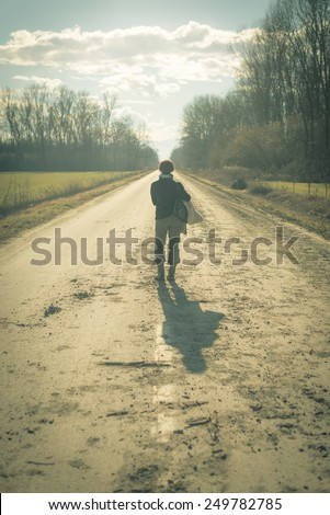 One lady with suitcase waiting alone in the middle of a country road  passing through fields and woods. Shot in backlight, filtered retro look, decontrasted and toned image. - stock photo
