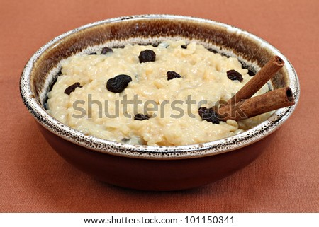 One large country crock bowl of creamy rice pudding with raisins and cinnamon sticks.  Close up, high angle view. - stock photo