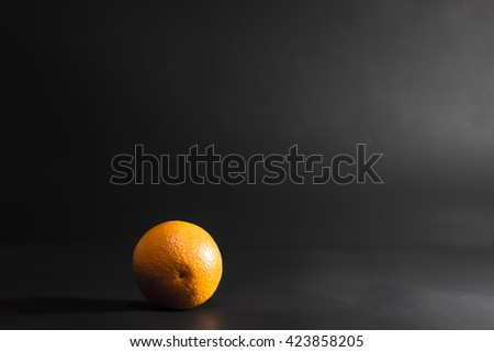 One large orange lies on a black background