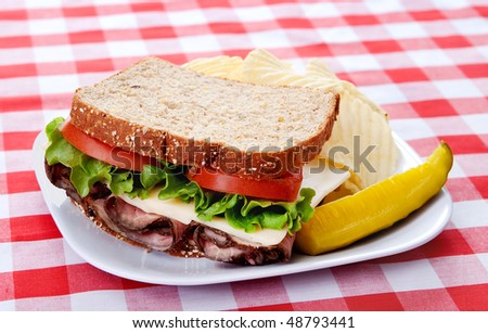 one large roast beef sandwich on oat bread with tomatoes and lettuce on a plate with classic red and white checkered tablecloth - stock photo