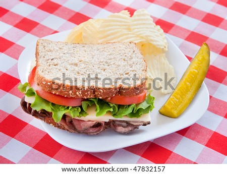 one large roast beef sandwich on oat bread with tomatos and lettuce on a plate with classic red and white checkered tablecloth - stock photo