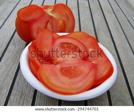 One large tomato on teak wood - stock photo