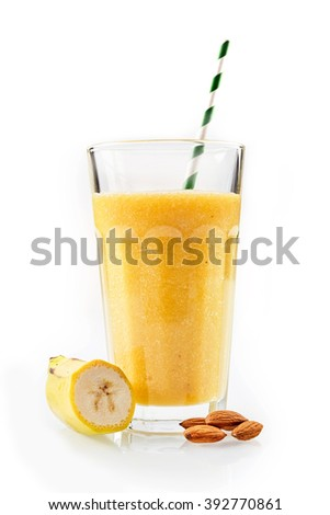 One large yellow banana and almond blended drink with a straw standing next to cut fruit and nuts against a white background
