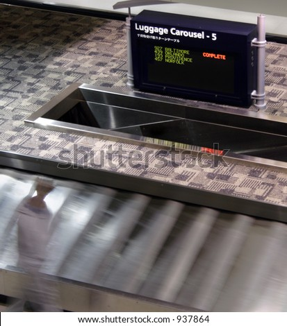 One last traveler waits for his luggage to arrive - stock photo