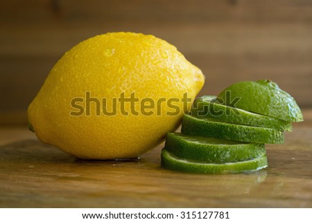 One lemon and many lime slices on wood background