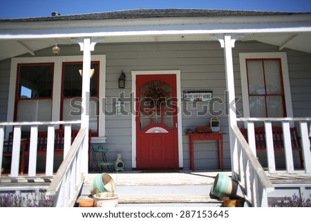 One level ranch home with cozy wrap around balcony deck on sunny day with blue sky - stock photo