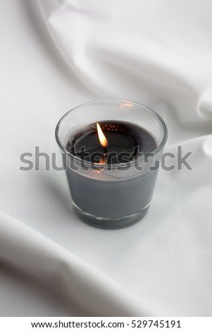 One light candle burning brightly in the background. Spa candle on light background. burning candles, zen concept. Zen candles. Spa and wellness setting with candles and silk towel. Day spa nature.